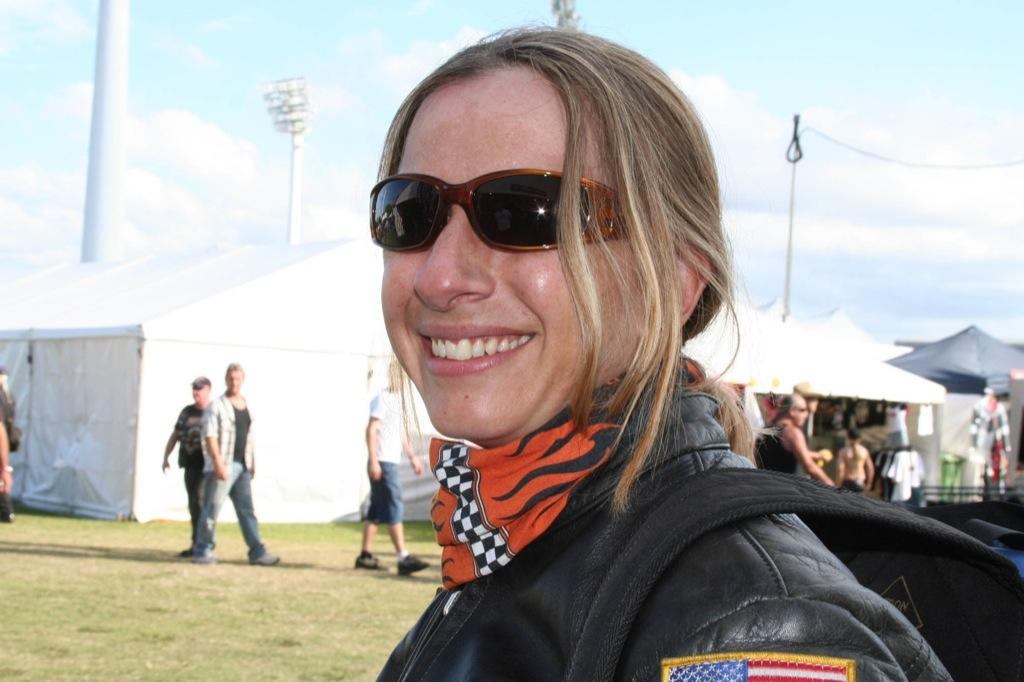 A side landscape shot of a woman in motorcycle leather gear. Kath is wearing a Original Buff® as scarf and smiling into the camera. I took the photo because I was amazed how straight and nice her hair was after having the helmet on for hours. She had the Original Buff® on as hair cover whilst wearing the helmet. The background shows the 2004 Gold Coast Bike Week with marquees and people leisurely walking around. Source: Edward Copyright: ©2004 Buff Downunder Pty Ltd