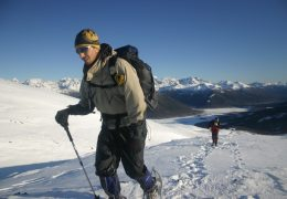 A side front landscape photo of two people snowshooing up a snowfield. In front is a man in full cold weather hiking gear. You can see him sweating in his face. On his head he is wearing a Original Buff® as beanie. The design is a custom design for the Patagonia Adventure Race. The other person is tracking about 50 metre behind. Source: buff.eu © Distributed for the promotion of the Original Buff® in outdoor / adventure