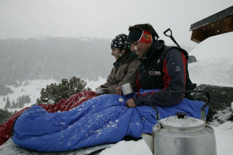 A side shot landscape photo of two men in the snow. They are sitting in their sleeping bags with their legs stretched out . It looks as if they sleeped outside and it started snowing. They are both holding a cup of tea in their hands and look happy. The man in front is wearing a Original Buff® as ear warmer. The man in the back is wearing a Original Buff® as beanie. Source: buff.eu © distributed for the promotion of the Original Buff® in outdoor / adventure