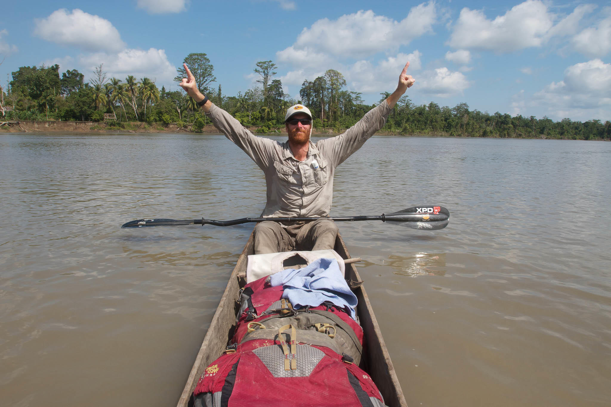 A frontal shot landscape photo of a man in a canoe raising his arms as a sign of victory. It is Andrew Johnson on the Sepik River in Papua New Guinea. He is wearing a Visor® Buff® as legionnaire style cap. The scene looks hot & humid. Image taken during the first spring to sea traverse of the Sepik River in Papua New Guinea. Source: Clark Carter © Clark Carter. https://www.adventureplaybook.com/ permission to use on our websites