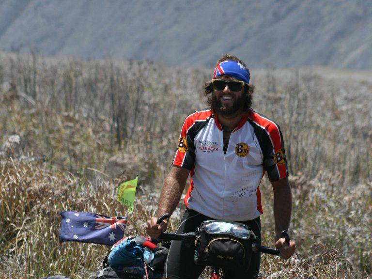 The horizontal image is a frontal shot of a man on a bicycle tour. It's Rian from EatSleepSurf.com. He has stopped in a field and is smiling at the camera. Rian is wearing Buff® team wear and a Australia Flag Original Buff®. It's obvious that non of the fabrics are wet or clingy. The location is in the highlands of Indonesia. It looks hot. But there are signs that there is also a chilly breeze. Rian is wearing his Original Buff® in layers. His flags on the bike are also flying. Source: EatSleepSurf.com.au Copyright: EatSleepSuf.com.au