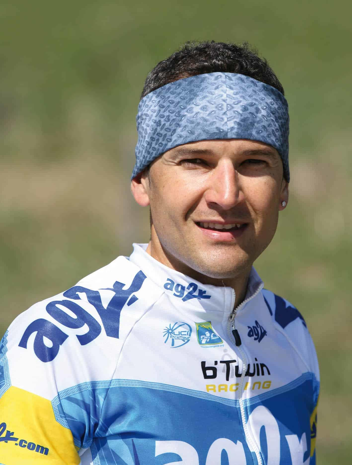 The photo shows a frontal upper body shot of Cyril Dessel before a 2006 Tour De France stage. He is wearing his AG2R team jersey and a Original Buff® as headband. The shun is shining and he looks at ease. Source: buff.eu Copyright: Distributed for the promotion of Original Buff® products