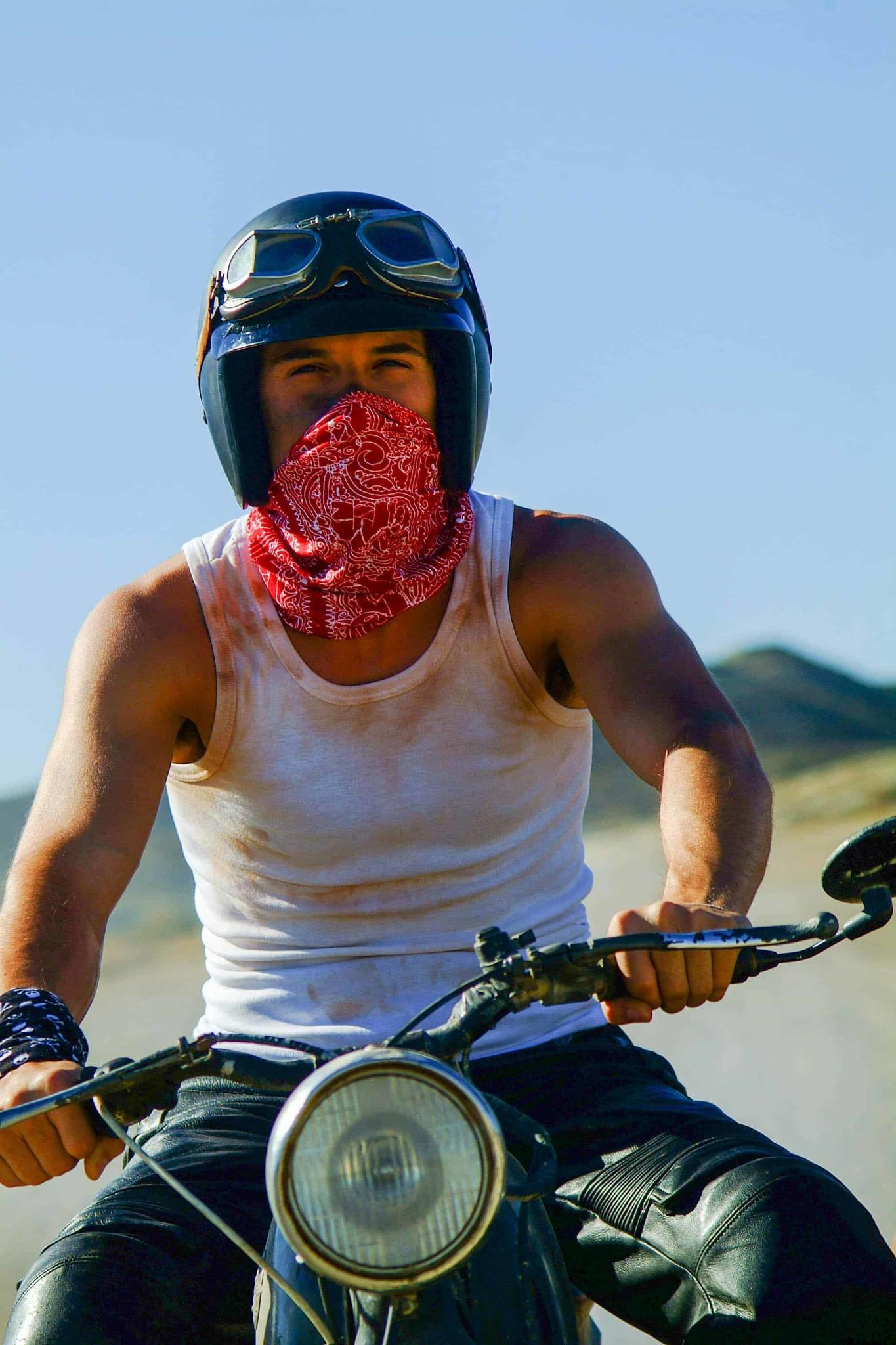 A frontal shot portrait photo of a man on a vintage motorbike. The man is wearing a leather bike trouser and a white singlet. Has a one High UV Buff® as wristband on and one High UV Buff® as face mask. He is also wearing an open face motorbike helmet and vintage motorcycle goggles over the helmet. The background looks hot & dusty. Source: buff.eu Copyright: Distributed for the promotion of the High UV Buff® in the motorcycling
