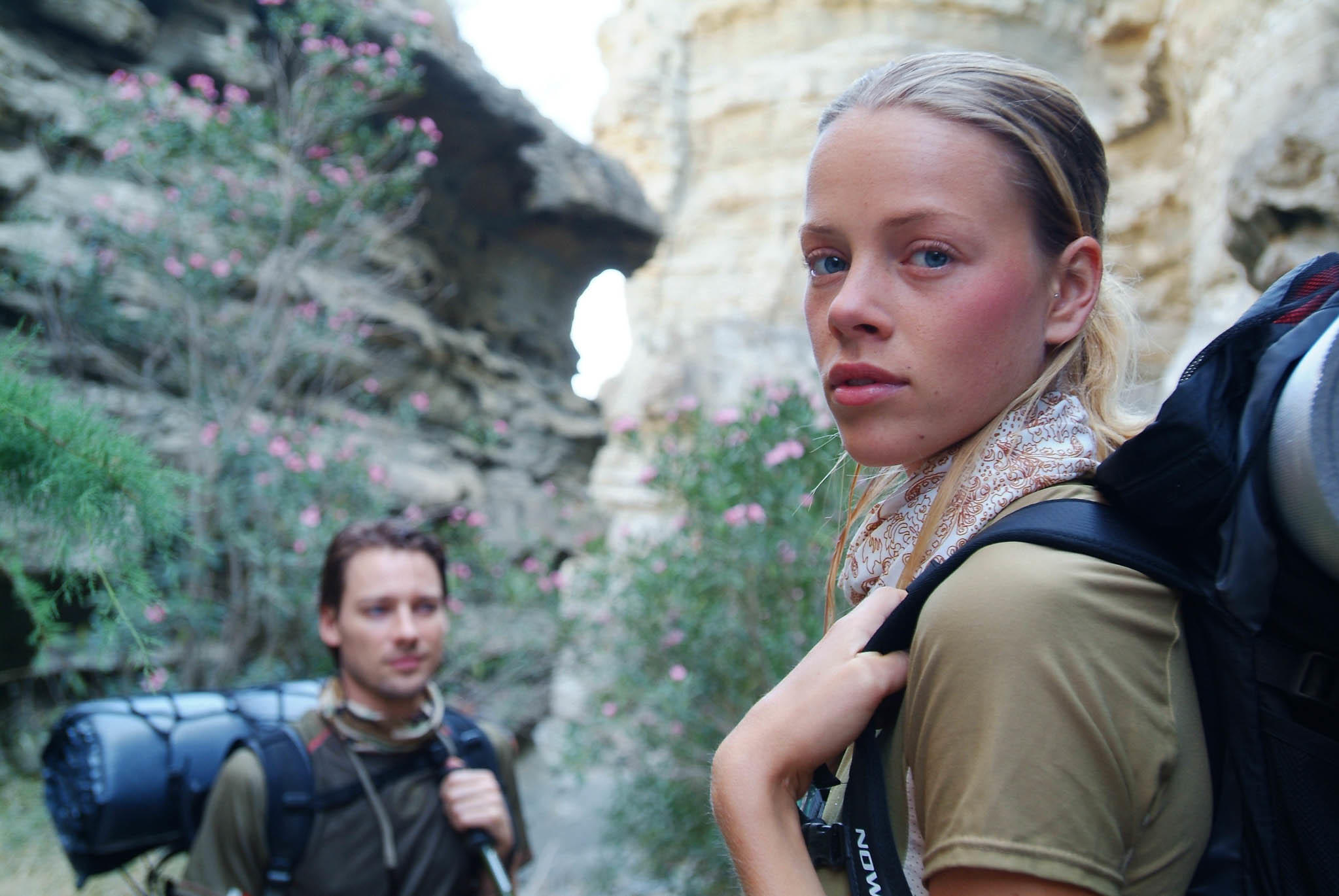 A side landscape shot of a woman and a man hiking in a gorge. Both are wearing Original Buff® as neck cooler. The woman to the front right is looking over her left shoulder into the camera. The man in the background seems distracted. The scene looks warm. Both are wearing summer hiking gear. Source: buff.eu © distributed for the promotion of the Original Buff® in hiking / trekking