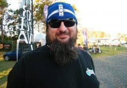 A landscape upper body shot of a bearded man looking straight into the camera. He sports a long beard, dark sunglasses & a Eureka Flag Original Buff®. He wears the Buff® as a bandana / pirate cap with the Eureka flag prominently on his forehead. He clearly identifies as a biker on a motorbike event. The photo was taken on the 2010 Wheel Babes Meeting in Ballina, NSW, Australia. The man was helping out as volunteer. Source: Edward Copyright: ©2010 Buff Downunder Pty Ltd