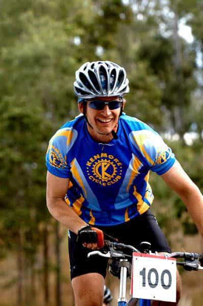 "The image shows John from Kenmore Cycles during the 2004 Kooralbyne 24 hour MTB XC race. He is wearing a Original Buff® as legionnaire cap under his helmet. This keeps the sweat out of his eyes and gives heat relief. I mention the High UV Buff® in the caption because today this would be your preferred product for this situation. The High UV Buff® excels in handling sweat & heat. The photo is a vertical shot showing John from the handlebars upwards. John is smiling and it looks as if he is having a great time. He is wearing mountain bike gloves, a short sleeved ""Kenmore Cycle Club"" cycling jersey, blue tinted sunglasses and a helmet with big vents. The Buff® is clearly visible under the helmet. Photographer: Unknown Copyright: Unknown but we received the images as part of being sponsors with the right to use commercially"
