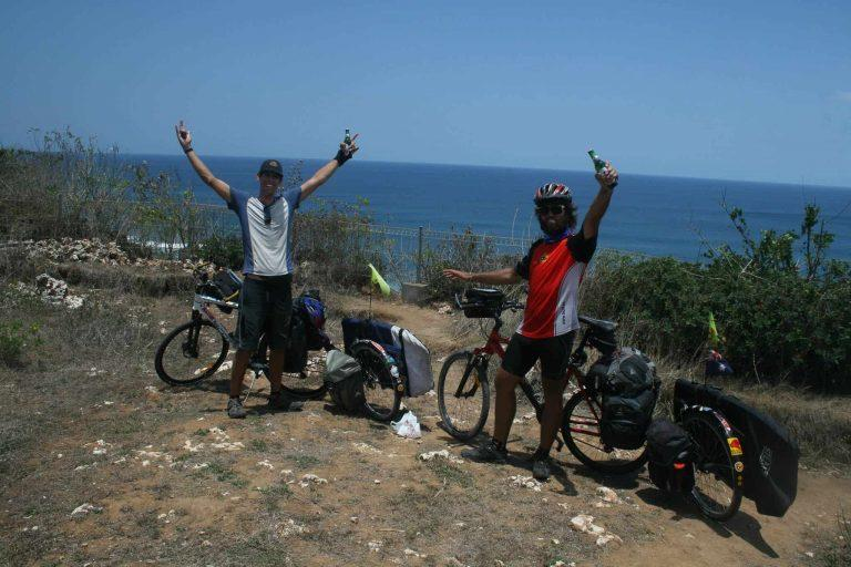 "The horizontal photo shows Rian and Dylan standing with their bicycles on the cliff of Uluwatu, Bali, Indonesia. They have cycled Indonesia from North to South and are celebrating their successful journey. Dylan is holding both arms up as a victory sign. Rian has got one arm up. He is holding a beer. Rian is wearing the Australia Flag Original Buff® as neck cooler. It appears mid day with hardly any shadow and a clear blue sky. It must be hot. Source: Eatsleepsurf.com.au Copyright: Unknown. We received the images as ""Thank You"" for providing the Buff®"