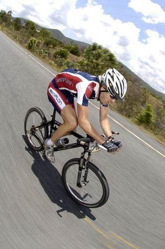 "A vertical photo of a male riding a XC mountain bike in the centre of a bitumen road. The rider is wearing a red & blue Simplon team jersey and cycle shorts. Under his white mtb helmet you can spot the Crocodile Trophy High UV Buff®. He is wearing it as a legionnaire cap covering his head and his back neck. The speed is fast paced and the surroundings looks like the can fields north of Port Douglas in North Queensland. Source: Crocodile Trohpy Photographer unknown Copyright: Unknown. We received this low-res images as ""Thank-You"" for providing the High UV Buff®"