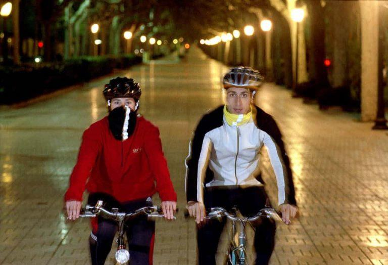 The horizontal photo is a frontal shot of a woman and a man riding bicycles in a city mall. It is dark and both are wearing cold weather gear. The woman on the left is wearing a Reflective Buff® as face mask. The man on the right is wearing a Reflective Buff® as scarf. Source: buff.eu Copyright: Unknown. Distributed for the promotion of the Reflective Buff®