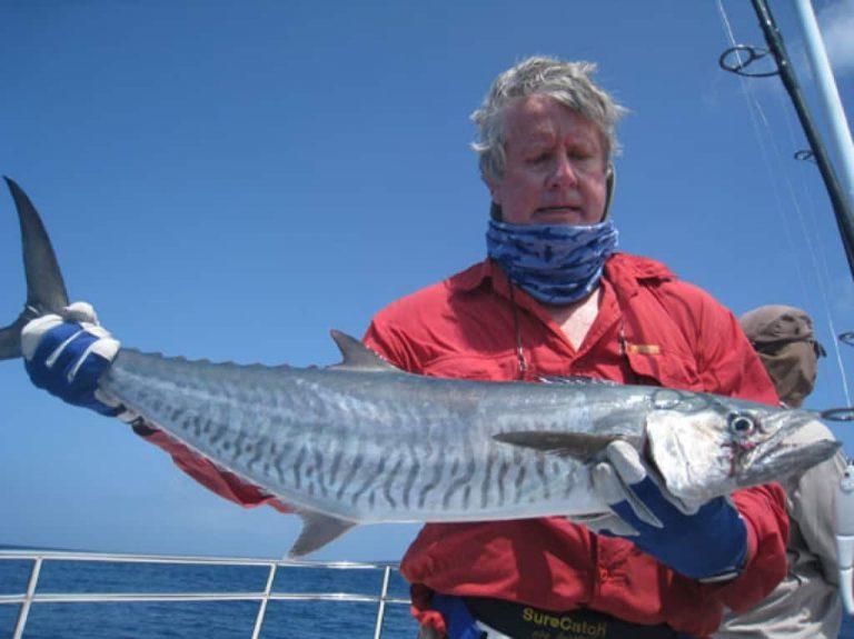 The landscape photo shows a middle aged man holding up his catch. He is wearing a Fishing High UV Buff® as scarf with the top covering his chin. The scenery looks like offshore fishing charter as the man wears tough leather gloves. Source: Unknown Copyright: Unknown
