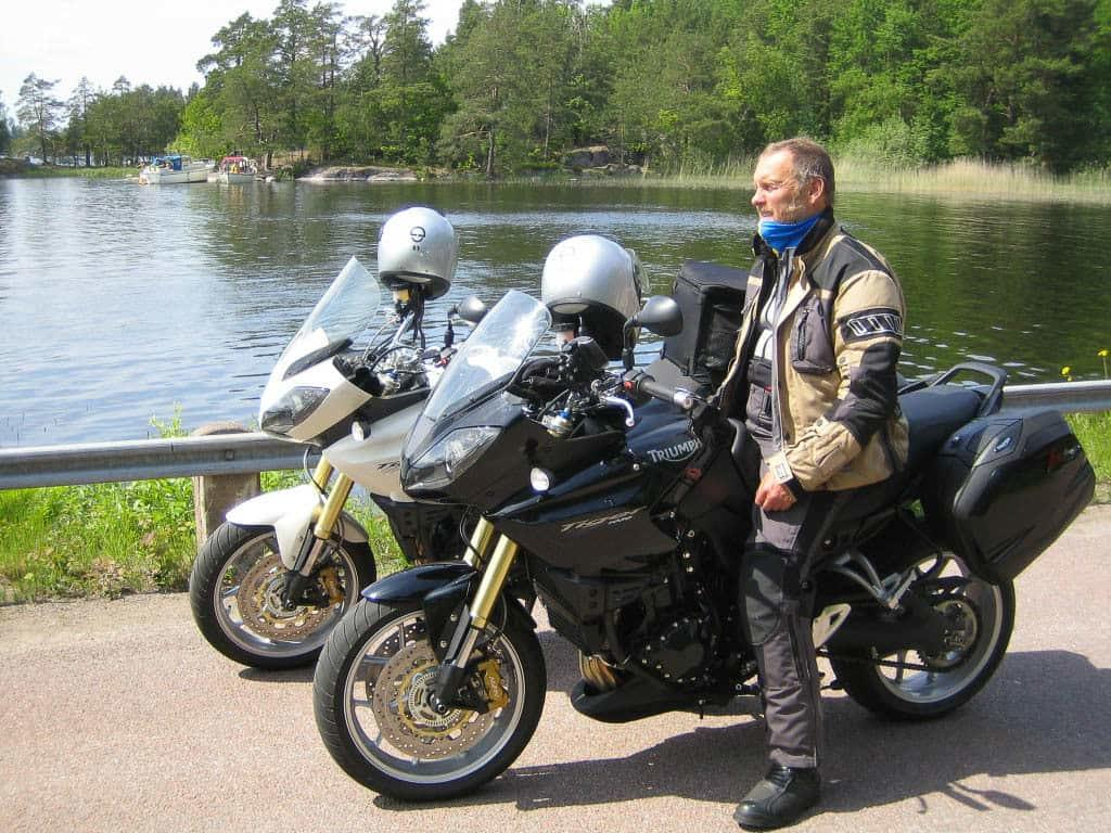 A side landscape shot of a man sitting on his touring motorcycle. It is the Norwegian Buff® distributor on a tour through Norway. He wear full motorycle touring gear and a blue Original Buff®. Look closer and you can see the Buff® as scarf around the neck with the top pulled up over the chin. The weather looks like Norwegian Summer. Nice but on the cooler side. Source: buff.eu Copyright: Distributed for the promotion of the Original Buff® in motocycle touring