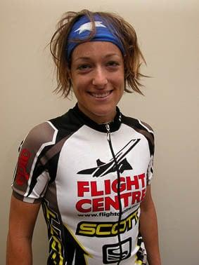 "The photo is vertical and shows female MTB rider Tory standing upright in front of a grey wall. She is wearing a Flightcentre Scott team cycle jersey and a Original Australia Flag Buff® as Alice Band. Her tired smile and her hair suggest that the photo is taken after a XC race. She smiles tired but happy. The Buff® as Alice Band keeps her hair together and tidy. Photographer: Unknown Copyright: Unknown. We received the image as a ""Thank-You"" for providing the Flight Centre Scott MTB team with Australia Flag Buff®"