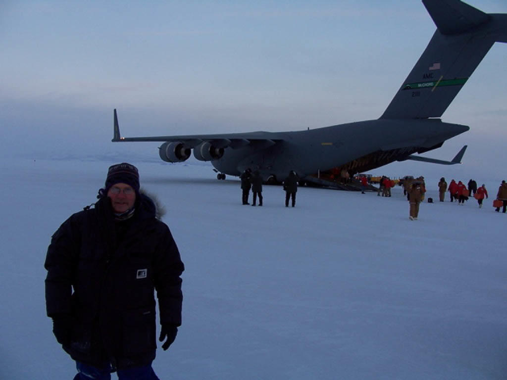 A front landscape shot of a man standing on an ice field in front of a large military supply air craft. The back loading dock is open and people are moving around the plane. It is the runway of the Scott Base in Antarctica. The man is wearing a one piece down overall with a fur hood. Around his neck is a Original Buff® as scarf. Source: Michael Nottage © permission to use on our website