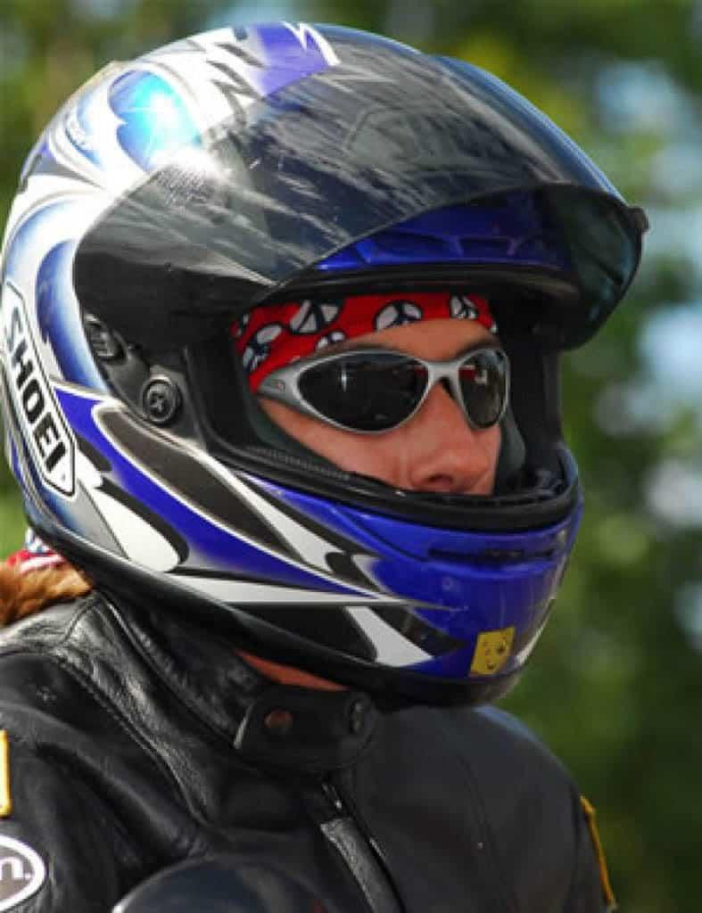 A portrait shot of a female motorcycle rider wearing a full face helmet. Kath is wearing a Original Buff® as helmet liner. She is also wearing a motorcycle leather jacket and sunglasses. Source: Kath Salotti © permission to use on our websites