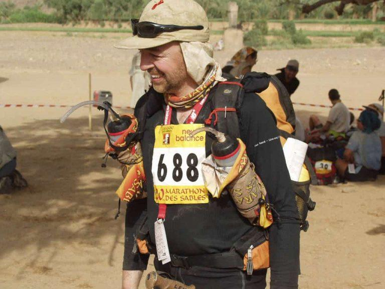 A side, landscape shot of a man smiling in full Marathon Des Sables gear. He is wearing a Original Buff® as neck cooler. He looks happy & relaxed. I assume that this photo was taken before a stage of the 2005 Marathon Des Sables. You can also spot other uses of the Original Buff® like water bottle covers. Today people prefer the High UV Buff® for this event. Source: buff.eu © distributed for the promotion of the Original Buff®.