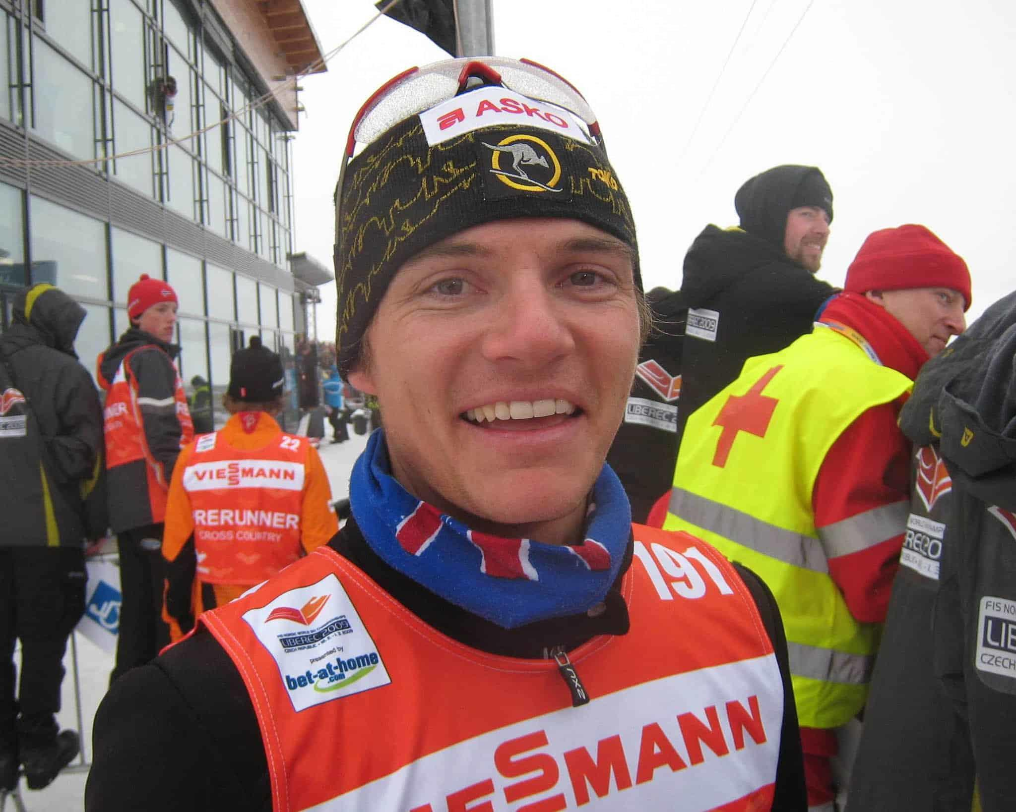 A landscape frontal shot of a joung XC skiing athlete before a race. It's Ben Sim smiling into the camera during the 2009 World Championships. He is wearing a Australian Flag Original Buff® as warming scarf. This way sweat doesn't cause any chill around the neck. Source: Finn Marsland © permission to use on our websites for the promotion of the Original Buff® in cross country skiing