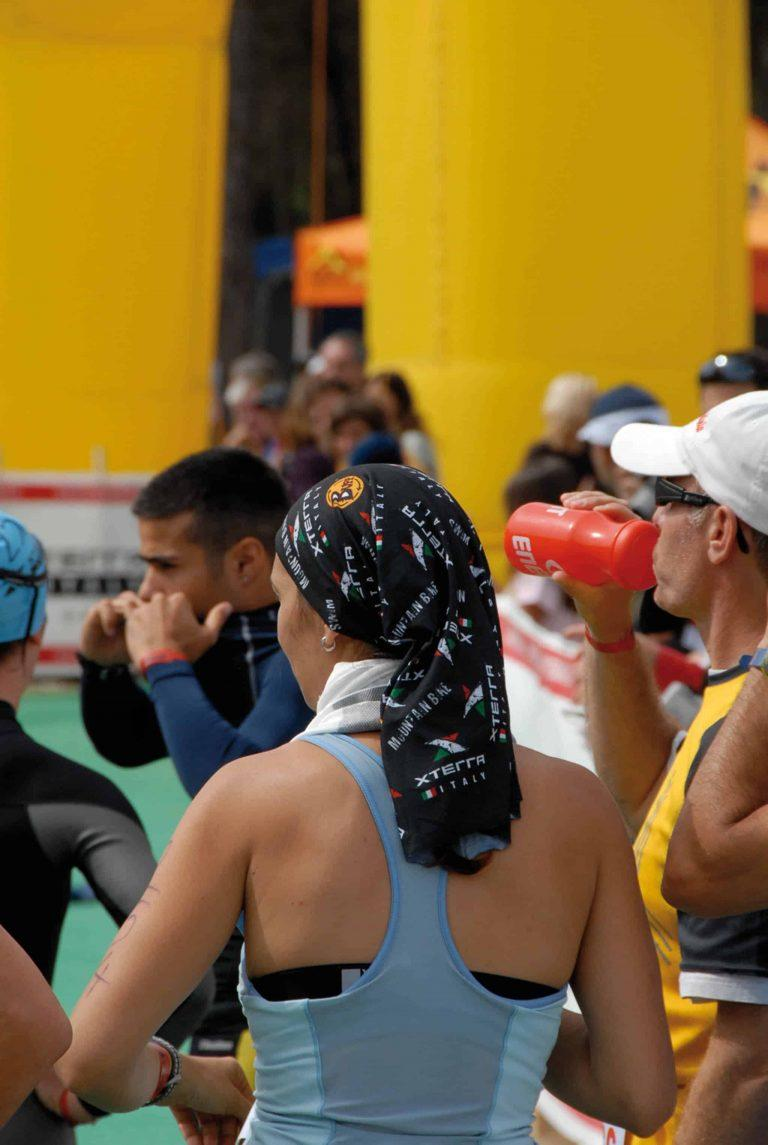 A back portrait shot of a woman standing in a triathlon race crowd. She is wearing a High UV Buff® as hair cover. This is a way to tame and dry your wet hair after the swim. Source: buff.eu © distributed for the promotion of the High UV Buff® in running / triathlon