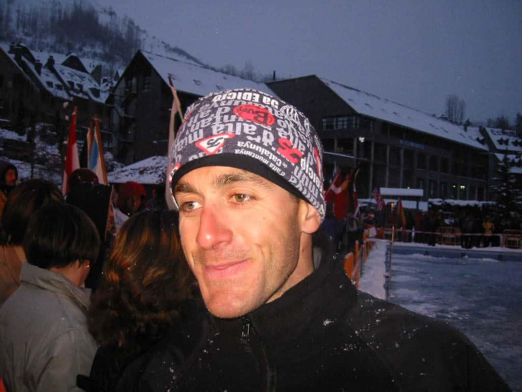 A landscape side shot of a man wearing a Polar Buff® as hat / beanie. It looks like it's apres ski time in a ski resort. There are a lot of country flags displayed so I assume it is an international event. The man looks happy with slightly glassy eyes. He seems to be in his comfort zone.