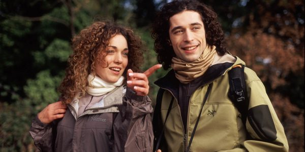 A landscape frontal shot of a young man & woman in the woods. They seem to be on a day trip outdoor. It looks like a standard European winter day without rain. Both are wearing premium outdoor jackets and Wool Buff® around their neck. Source buff.eu © Distributed for the promotion of the Wool Buff®