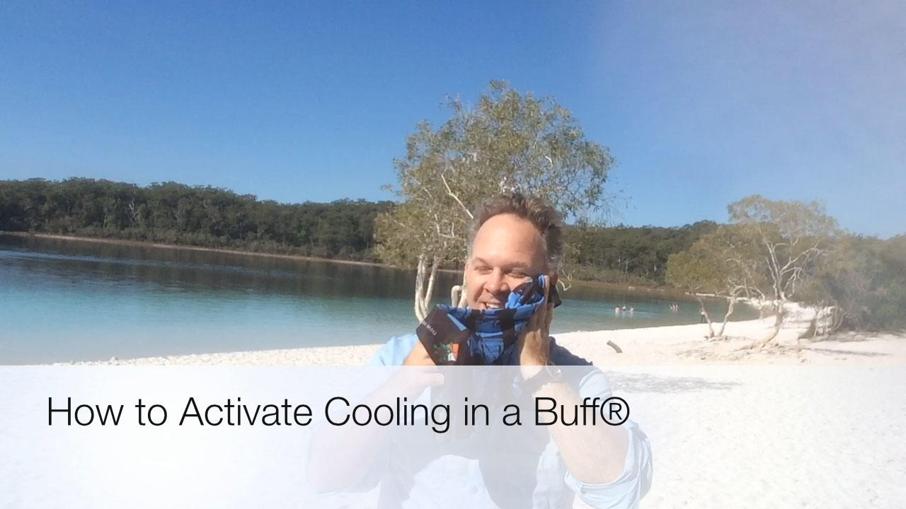 """A landscape image with overlay intro header """"How to Activate Cooling in a Buff®"""". It shows Edward at Lake McKenzie, Fraser Island, holding a Original Buff® to his face. In the background you can see the lake and people swimming in it. © Edward Omagbemi"""