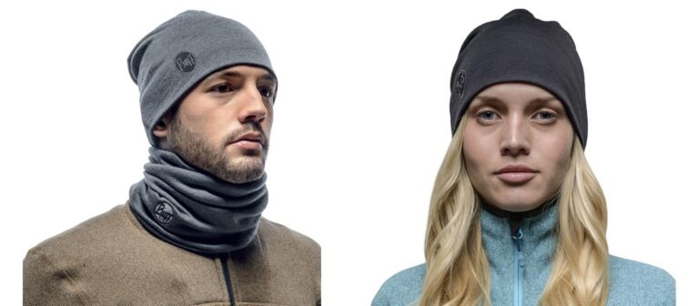 A montage of two studio shots. On the left is a male model wearing a solid grey Heavyweight Merino Wool Loose Hat and a Thermal Neckwarmer Buff®. On the right is a female model wearing a solid black Heavyweight Merino Wool Loose Hat. Source: Buff.eu