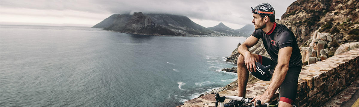 A wide format image of a male cyclist stopping at the side of the road and looking at the scenery. You can see a large body of water and an island in the background. The man is leaning against a rock wall type road boundary. Source: buffusa.com