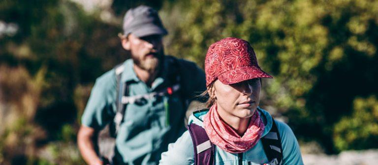 A catalogue hero photo of a man and a woman hiking. They are wearing cool environment clothing with a Buff® around the neck and a Pack Treck Cap on the head. The woman in the foreground is sharp and in focus. The man in the back and the background are blurry. Source: buff.eu