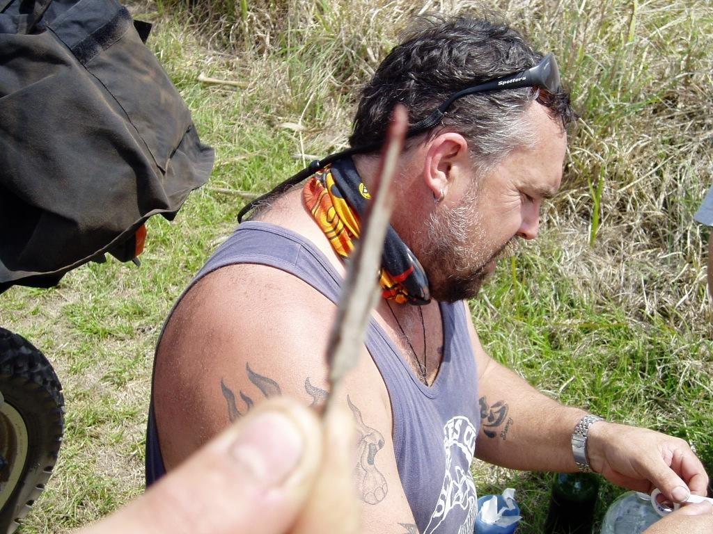A male motorbiker with a grey Ulysses Club singlet sitting on the ground and having a rest