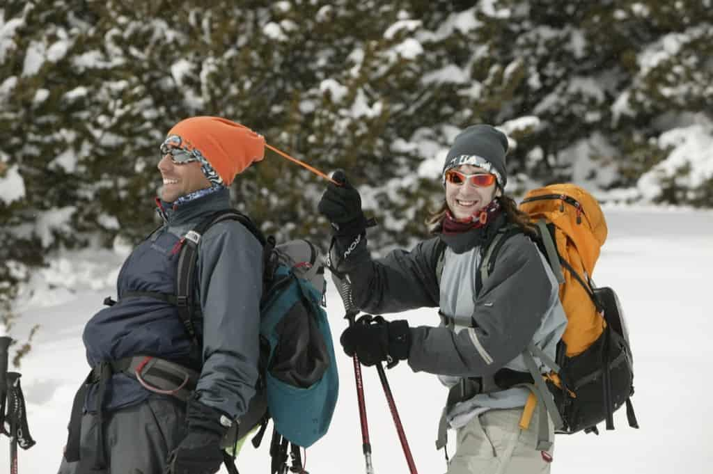 A man and a woman walking in winter sport gear through the snow. The woman is walking behind the man and pulling a drawstring on his Buff® Polar Neckwarmer. The photo is a photoshoot for the promotion of the Buff® Polar Neckwarmer. Source: buff.eu