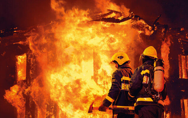Two structural firefighters standing in front of a burning house in full protective gear. The flames are shooting out of the windows and the scene looks very hot. Source: buff.eu