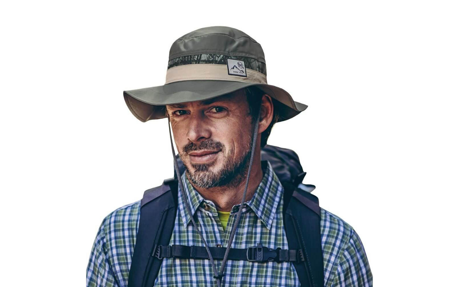 A studio photo showing a mid-aged man wearing a Buff® Booney Hat. The man is wearing a checkered flannel shirt and wearing a day backpack. He is looking into the camera. Source: buff.eu