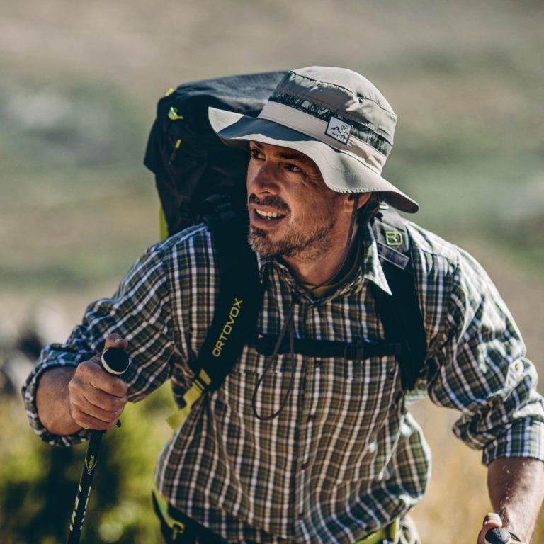 Picture of a man hiking up a hill. It looks sunny and hot. The man is wearing a Buff® Booney Hat and is carrying a backpack. He is also using walking poles. Source: buff.eu