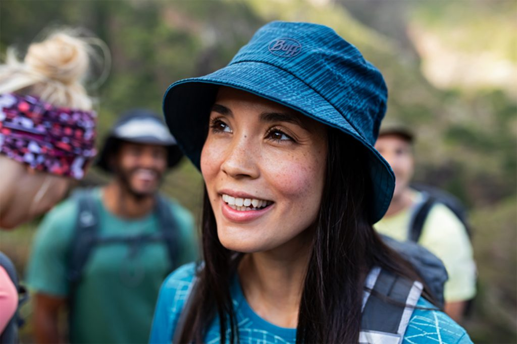 A promotional photo showing a group of male and female hikers. The woman in the front of the scene is sharp while all others in the background are blurred. The woman is wearing a BUFF® Trek Bucket Hat. She is looking at something behind the camera in the distance. Source: buff.eu