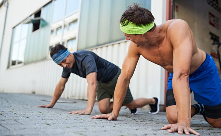 2 men outside a CrossFit training centre doing push-ups. They are both wearing the BUFF® Fastwick Headband and smiling. Source: buff.eu