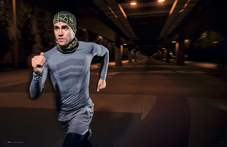 A photo of a young man running at night through a city. The reflective elements of the BUFF® DryFLX are clearly visible. Source: buff.eu