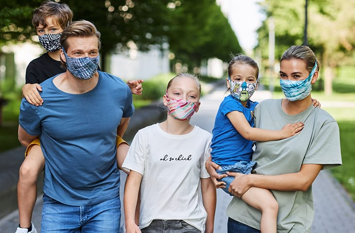 A young family with 3 kids wearing BUFF® Filter Masks in a park setting. Source: buff.eu